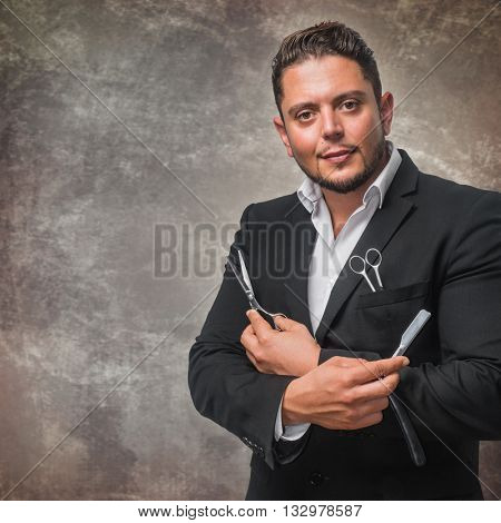 Portrait of a young professional hairdresser or barber with his tools