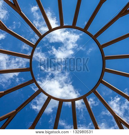 Steel structure with the shape of the sun and blue sky on the background.