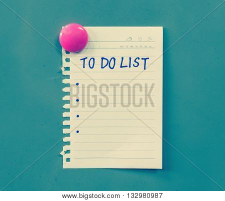Hand writing on paper with to do list words attached with pink magnet on steel board colored filter effect