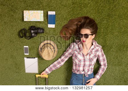 Portrait of beautiful tourist lady in sunglasses lying on green grass among mobile or smart phone, passport, cap, map or guide, etc. Pretty woman with red lips posing for photographer.