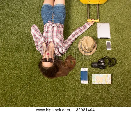 Picture of happy beautiful tourist lady lying on green grass and touching her face. Pretty woman lying among mobile or smart phone, passport, cap, map or guide, etc. while holding yellow luggage.