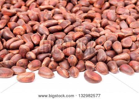 unpeeled pine nuts on a white background.