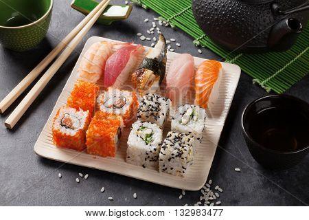 Set of sushi, maki and green tea on stone table