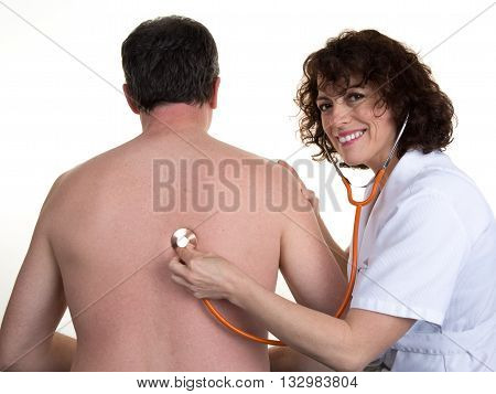 Doctor Female Listening To Man's Heartbeat In Clinic