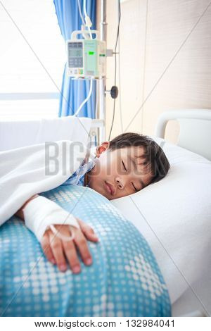 Illness asian boy sleeping at modern and comfortable equipped hospital room with saline intravenous (IV) on hand. Health care and people concept.