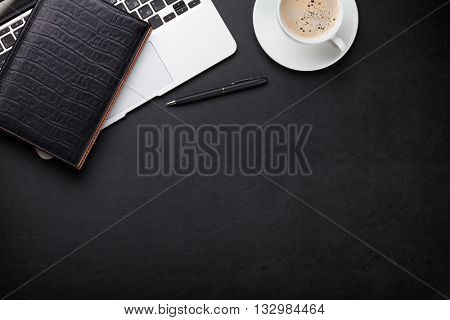 Office leather desk workplace table with laptop, coffee cup, notepad and pen. Top view with copy space