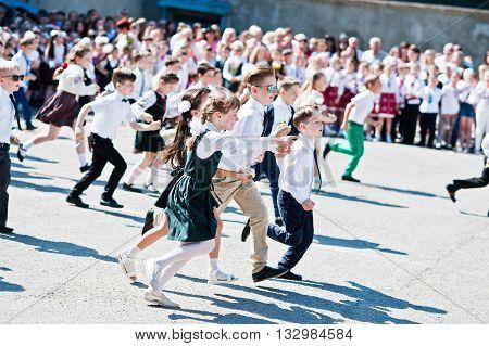 Bila, Ukraine - May 27, 2016: School Line Is In Schoolyard With First-grade Pupils And Teacher. Chil