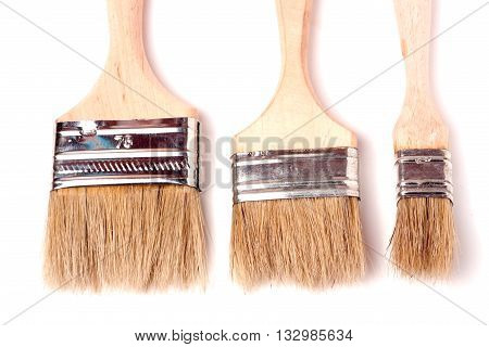 Three different size paint brushes isolated on white background.