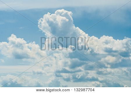 White cumulus clouds illuminated by the sun on the summer blue sky