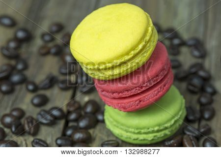 colourful french macaroons and coffee bean on wooden table