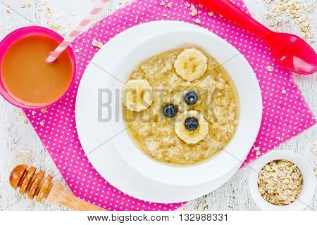 Baby healthy breakfast - oatmeal porridge with honey and banana in shape bear. Fun food idea for kids