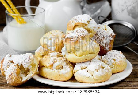 Eclairs or profiteroles from choux dough with cream filling, homemade baking traditional pastries French cuisine selective focus