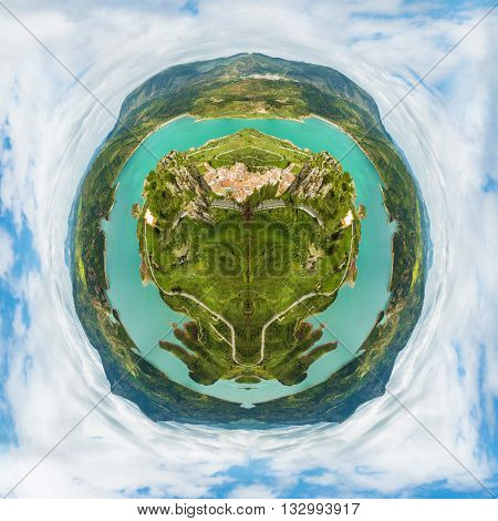 Little planet composition of an aerial view of the top of a green earth with trees and seas, in a cloudy blue sky. Concept of green ecosystem conservation.