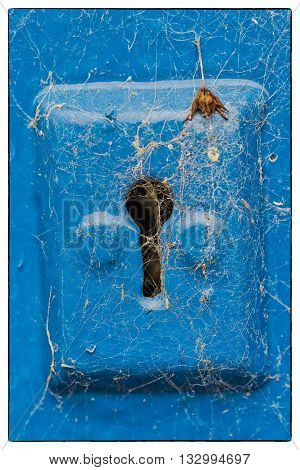 Cobwebs on a blue metail key hole of a blue wooden door. Vintage border