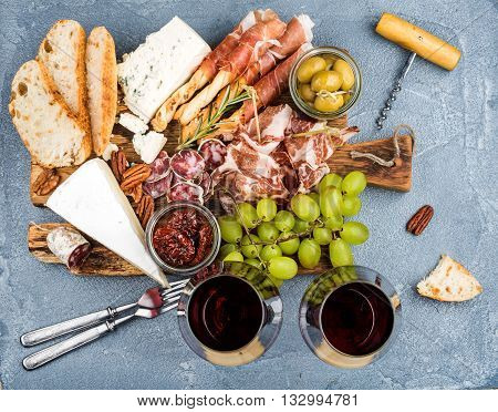 Cheese and meat appetizer selection. Prosciutto di Parma, salami, bread sticks, baguette slices, olives, sun-dried tomatoes, grapes and nutson rustic wooden board, two glasses of red wine over grey concrete textured backdrop, top view