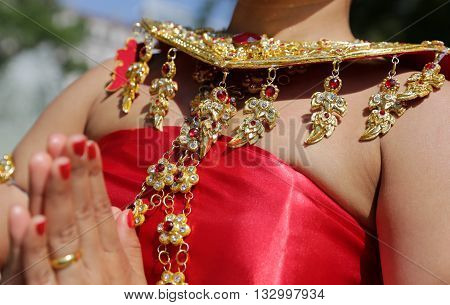 A female performer is showing traditional Thailand clothes and jewelries during a
