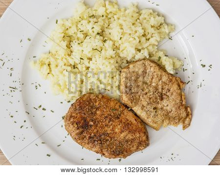 Pork tenderlion with rice on the white plate. Food theme. International cuisine. Restaurant menu.