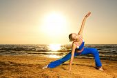 stock photo of athletic woman  - Beautiful young woman doing fitness exercise on a beach at sunset - JPG