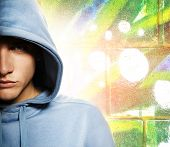 stock photo of break-dancing  - Cool looking man in a hood over abstract graffiti background - JPG