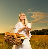 stock photo of household farm  - Beautiful young woman with a basket full of fresh baked bread and jug of milk - JPG