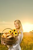 foto of household farm  - Beautiful young woman with a basket full of fresh baked bread - JPG