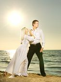 image of ballroom dancing  - Young couple dancing on a beach at sunset - JPG