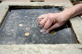 foto of wishing-well  - a woman putting money inside a well - JPG