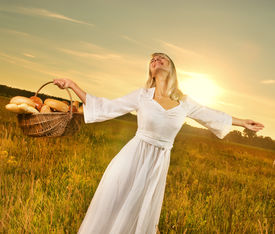 stock photo of beautiful young woman  - Beautiful young woman with a basket full of fresh baked bread - JPG