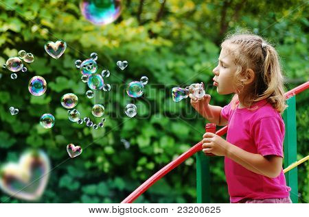 Little girl blowing interesting bubbles