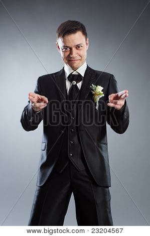 Handsome Man In Black Suit Pointing Fingers In Front Of Himself. Indicate Forward.