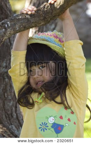 Cute Little Girl Hanging From A Tree