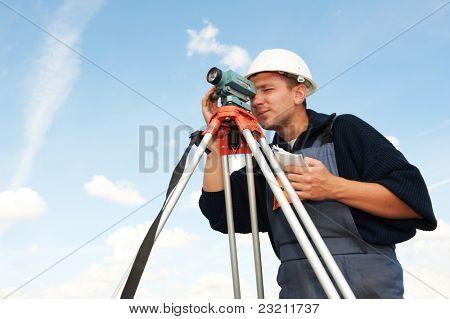 Ein Landvermesser Arbeiter mit Theodolit Ausrüstung im freien die Daten eingeben