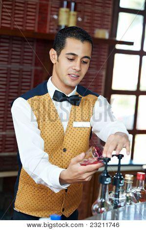 Cheerful arab barman in uniform preparing cocktail in his hand