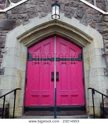 Old style magenta church doors on a stone building