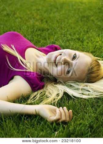 healthy blonde girl laying on the grass