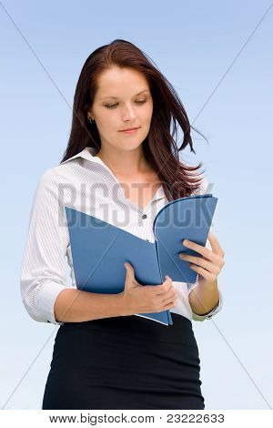 Businesswoman In Sunny Nature Looking Into Folders