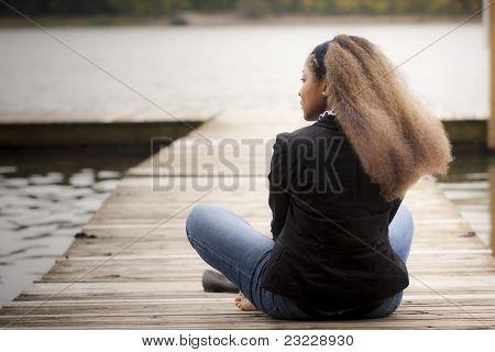 Woman sitting on quay