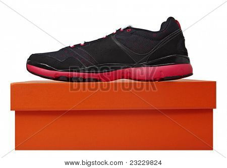 fun black and pink leather fitness sport shoe on the orange box isolated over white.
