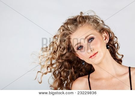 beautiful strawberry blond happy teenage girl with green eyes and long curly hair blowing in wind over grey studio background .
