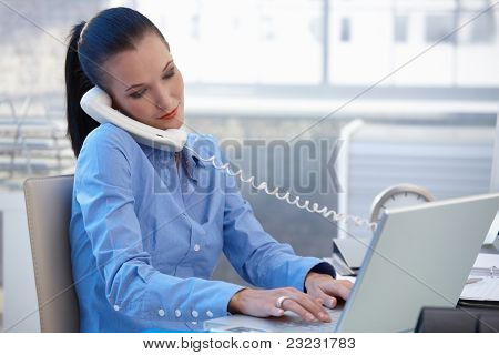 Busy office worker girl taking landline phone call while typing on laptop computer.?