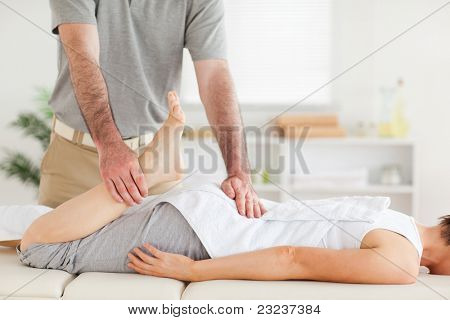 A chiropractor stretches woman's leg in his surgery