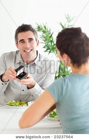 Smiling Man proposing to his surprised girlfriend during dinner in a restaurant