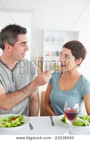 Man feeding his brunette wife in a dining room