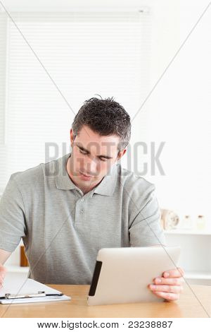 Doctor sitting at a table with a tablet and a chart in a room