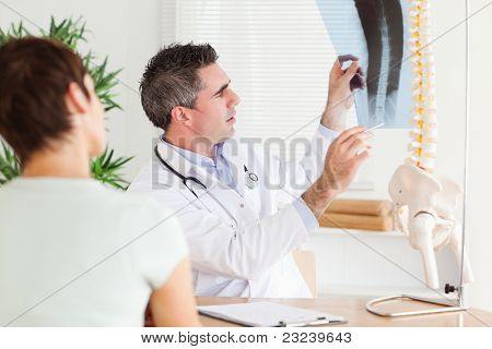 Male Doctor showing a female patient a x-ray in a room