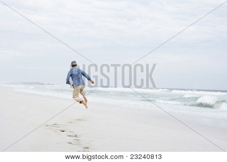 Senior man running and jumping on beach