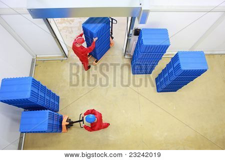 Aerial view of two workers loading plastic boxes  in small warehouse