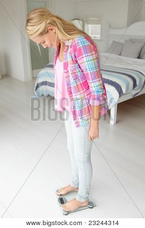 Teenage girl weighing herself