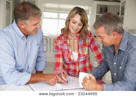 Mid age couple with financial advisor at home