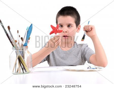 Cute boy painting sea star over white background.